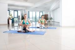 Милые женщины тренируя asana йоги Стоковая Фотография
