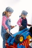 Милые маленькие двойные девушки ремонтируя автомобиль Стоковые Фотографии RF