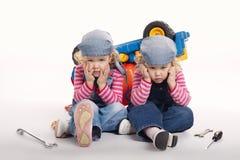 Милые маленькие двойные девушки ремонтируя автомобиль Стоковое Изображение RF