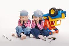 Милые маленькие двойные девушки ремонтируя автомобиль Стоковые Фото