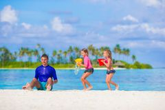 Милые маленькие девочки и отец имея потеху с пляжем Стоковые Изображения RF