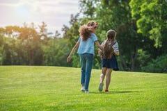 Милые многонациональные девушки идя совместно в парк Стоковое Фото