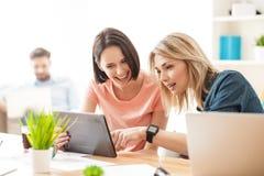 Милые молодые женские работники отдыхают в офисе Стоковое фото RF