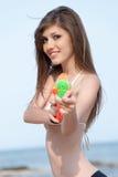 Милые молодые женщины играя с водяным пистолетом на пляже Стоковая Фотография RF
