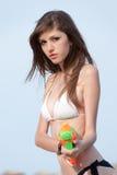 Милые молодые женщины играя с водяным пистолетом на пляже Стоковые Изображения