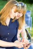 Милые молодые женщины используя smartphone в парке лета Стоковая Фотография