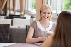 Милые молодые женщины отдыхают в кафе Стоковые Изображения