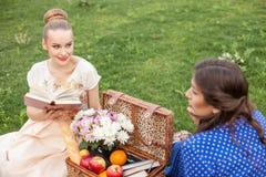 Милые молодые женщины отдыхают на пикнике Стоковое фото RF