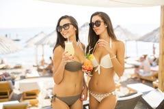 Милые молодые женщины с coctails на пляже Стоковые Фото