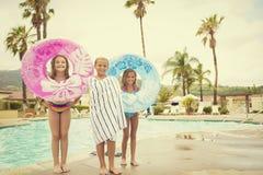Милые молодые парни играя в бассейне на летний день Стоковые Изображения
