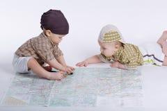 Милые младенцы планируя перемещение с картой Стоковое Фото