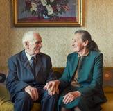 Милые 80 добавочных годовалых пожененных пар представляя для портрета в их доме Влюбленности концепция навсегда Стоковое Изображение RF
