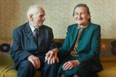 Милые 80 добавочных годовалых пожененных пар представляя для портрета в их доме Влюбленности концепция навсегда Стоковая Фотография RF