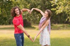 Милые пары в парке делая сердце формируют Стоковое Изображение