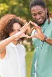 Милые пары в парке делая сердце формируют Стоковое Изображение RF