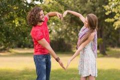 Милые пары в парке делая сердце формируют Стоковое Фото