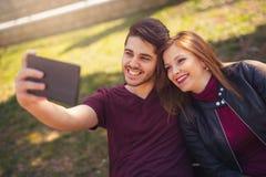 Милые пары делая selfie в парке Стоковые Изображения