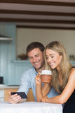 Милые пары используя smartphone совместно Стоковые Изображения