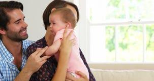 Милые пары сидя на софе и пробуя утихомирить их младенца сток-видео