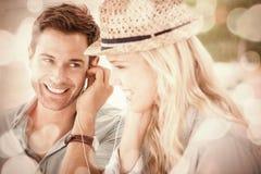 Милые пары слушая к музыке совместно в кафе Стоковое Фото