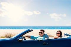 Милые пары управляя автомобилем с откидным верхом Стоковая Фотография