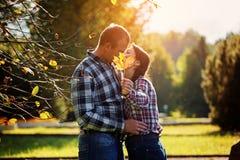 Милые пары outdoors в падении Прятать молодого человека и женщины целуя за кленовым листом Стоковые Фото