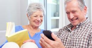 Милые пожилые пары используя smartphone сток-видео