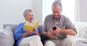 Милые пожилые пары читая или смотря ТВ акции видеоматериалы