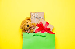 Милые подарки в красивых зеленых хозяйственной сумке и плюшевом медвежонке на выигранный Стоковые Фотографии RF
