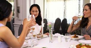 Милые подруги наслаждаясь едой совместно сток-видео