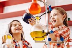 Милые радостные девушки используя научное оборудование Стоковые Изображения RF