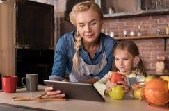 Милые рецепты чтения девушки с ее матерью в кухне Стоковое фото RF