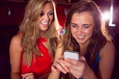 Милые друзья смотря smartphone совместно Стоковая Фотография RF