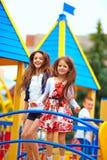 Милые счастливые девушки скача на игрушку рокируют спортивную площадку Стоковое фото RF