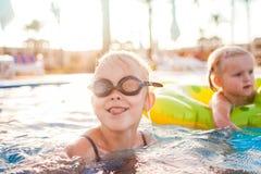 Милые счастливые маленькие девочки имея потеху в бассейне Стоковое фото RF