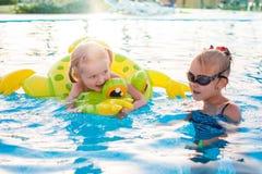 Милые счастливые маленькие девочки имея потеху в бассейне Стоковые Изображения RF