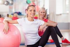 Милые тонкие девушки работают в фитнес-центре Стоковое фото RF