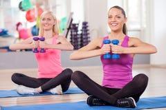 Милые тонкие женщины тренируют с оборудованием в спортзале Стоковое Изображение