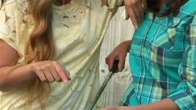 Милые усмехаясь девушки используя smartphone акции видеоматериалы