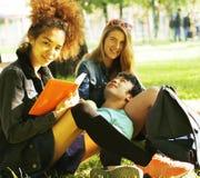 Милые teenages группы на здании университета с huggings книг, нациями разнообразия Стоковые Фото