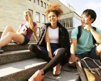 Милые teenages группы на здании университета с huggings книг Стоковые Изображения