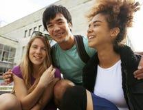 Милые teenages группы на здании университета Стоковые Изображения