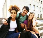 Милые teenages группы на здании университета Стоковое Фото