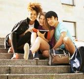 Милые teenages группы на здании университета Стоковое Изображение