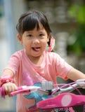 Милый азиатский велосипед езды девушки Стоковая Фотография