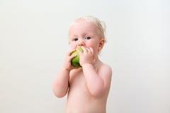Милый белокурый младенец есть яблоко Стоковая Фотография RF