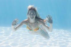 Милый белокурый усмехаться на камере под водой в бассейне Стоковая Фотография RF