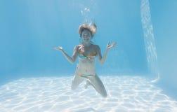 Милый белокурый усмехаться на камере под водой в бассейне Стоковые Изображения RF