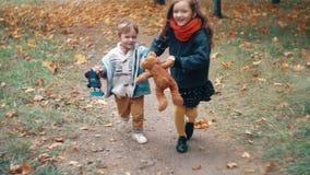 Милый брат и мальчик и девушка сестры бежать держащ руки, с их игрушками через переулок осени в парке медленном mo акции видеоматериалы