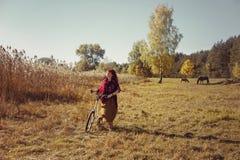 Милый велосипед катания девушки в поле Стоковые Изображения